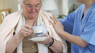 Una cuidadora atiende a una persona mayor.