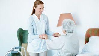 Una anfermera ayuda a una persona mayor.