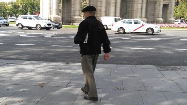 Una persona mayor pasea al sol.