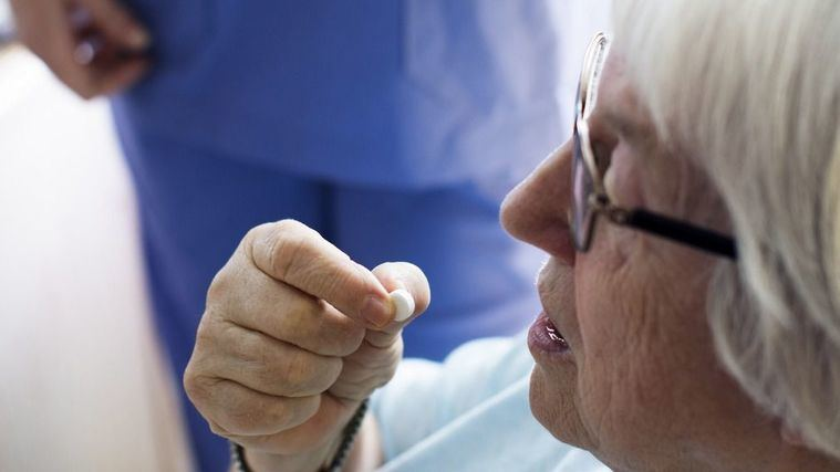 Enfermero da la medicación a una persona mayor.