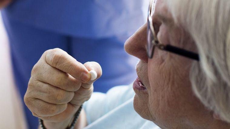 Enfermero da la medicación a na persona mayor.