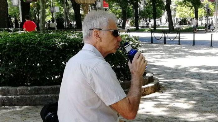 Hidratación, una persona mayor bebe agua en el parque.