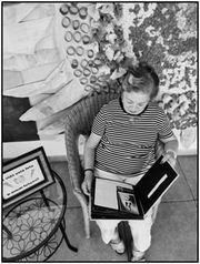 Mujer mirando su álbum de fotos en el Geriàtric Palafolls.