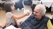 Una niña da de comer a una persona mayor en un centro Allegra.