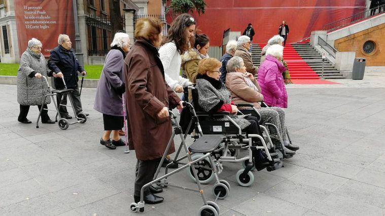 Un grupo de mayores, algunos dependientes, visitan un museo.