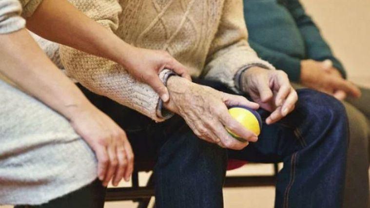 Personal sanitario cuidando a n mayor en una residencia.