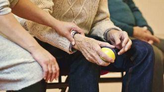 Personal sanitario cuidando a una persona mayor en una residencia.