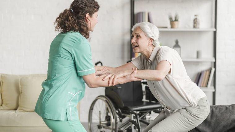 Una enfermera ayuda a una persona mayor en una residencia.
