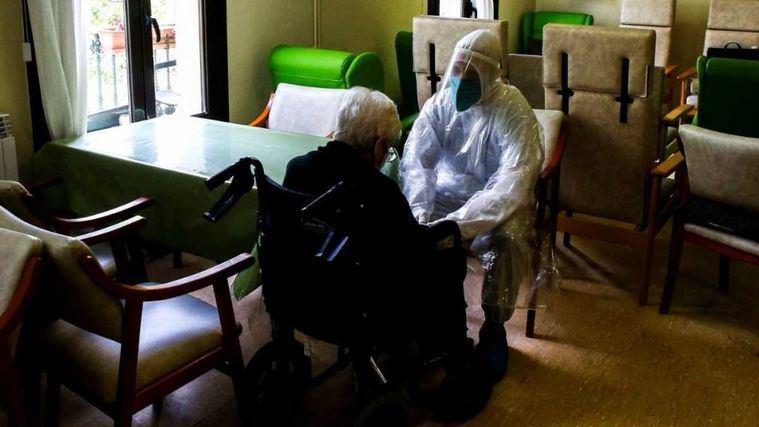 Un trabajador de una residencia conversa con una residente.