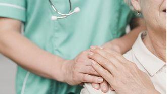 Una enfermera cuida a una persona mayor.