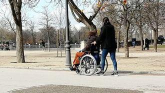 Un cuidador pasea con una persona dependiente.