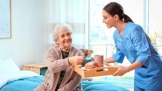Una enfermera atiende a una persona mayor en una residencia.