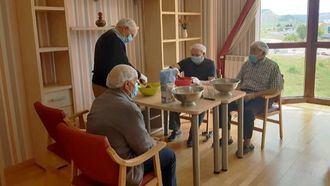 Los residentes de Emera Guadalara participan en un taller de cocina acompañados por su terapeuta ocupacional.