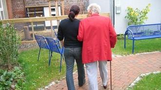 Un familiar pasea con una residente.