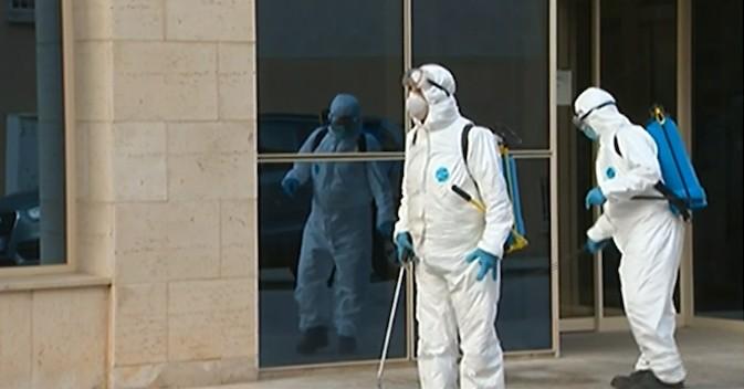 Operarios desinfectan la entrada de una residencia.